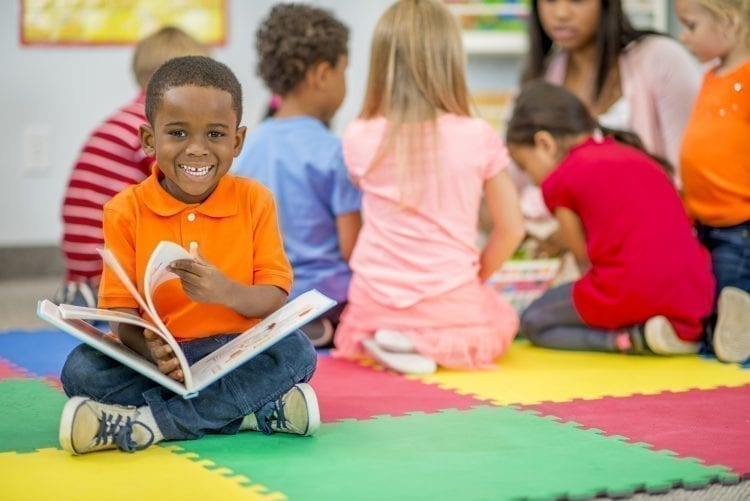 little boy holding a picture book and smiling at camera