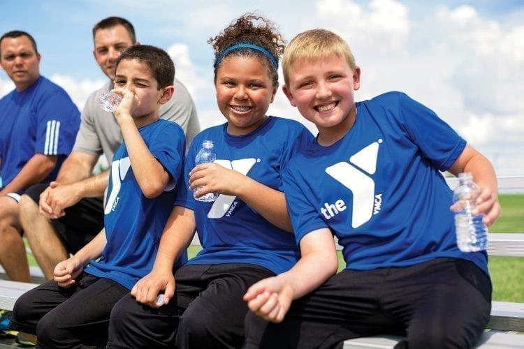 smiling kids wearing YMCA blue shirts drinking water