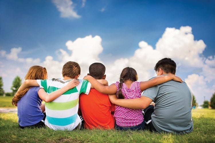 kids with arms around each other sitting in grass