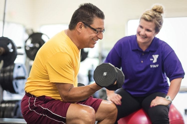 person lifting weights with trainer
