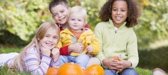 four smiling kids outside with pumpkins