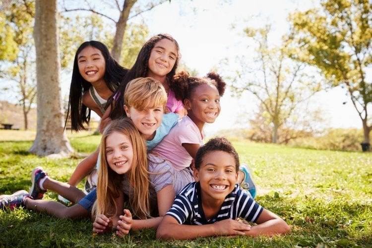 six smiling kids laying grass