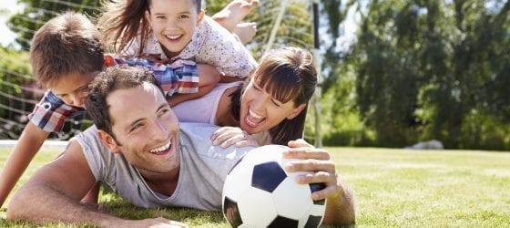 family smiling with soccer ball laying in grass