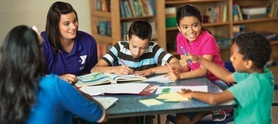 four kids working on homework with YMCA staff