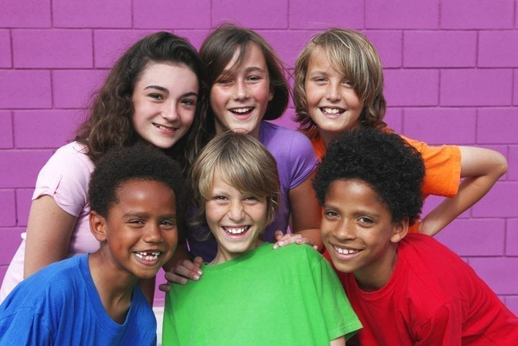 six kids smiling in front of purple brick wall