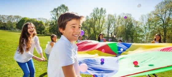 kids playing outside with parachute